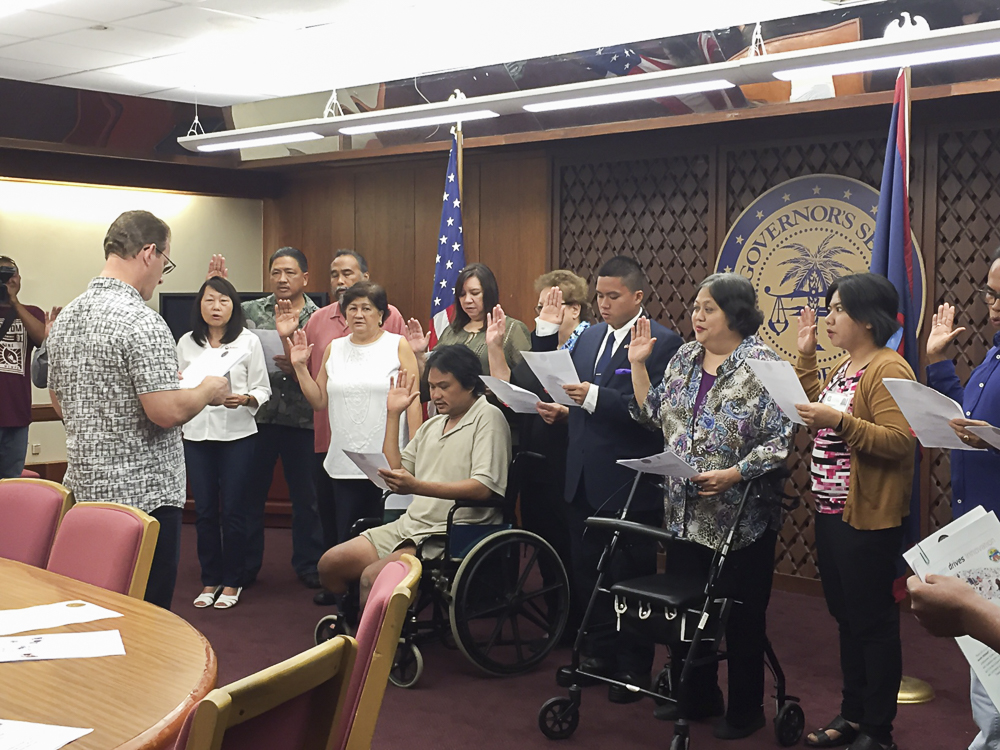 Acting Governor Ray Tenorio (Back facing the camera), swears in new members of the State Rehabilitation Council.